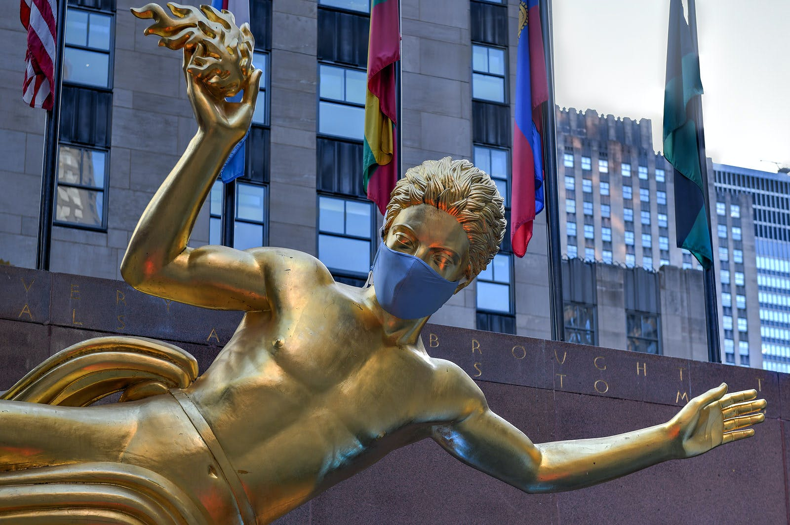 New York, NY / USA – Jul 2, 2020: Real estate firm Tishman Speyer fitted masks on Prometheus and other classic statues in Rockefeller Center to remind New Yorkers to wear COVID-19 face coverings.