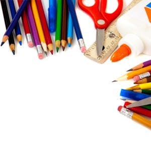 Assorted school supplies including pens pencils scissors glue and a ruler on a white background