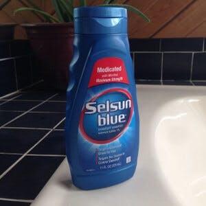 A bottle of Selsun Blue dandruff shampoo to ease eczema, under-breast rash with dandruff shampoo