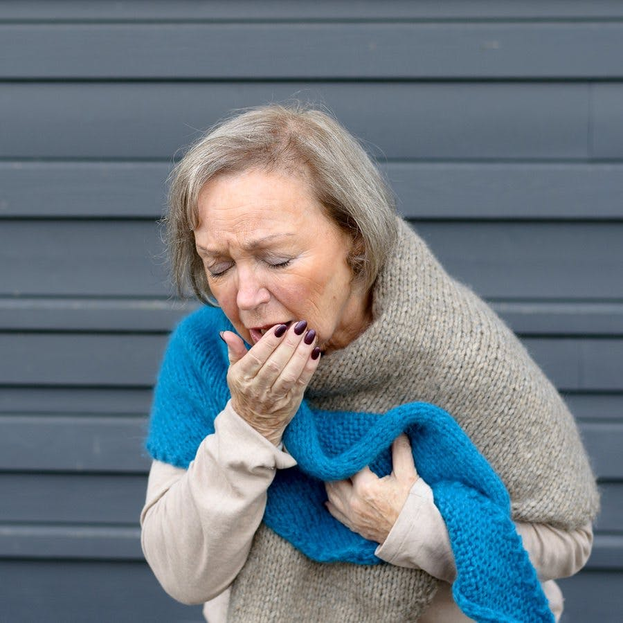 Elegant senior woman coughing into her hand while clutching her chest in a concept of seasonal bronchitis or influenza and medical healthcare grey metal background with copy space