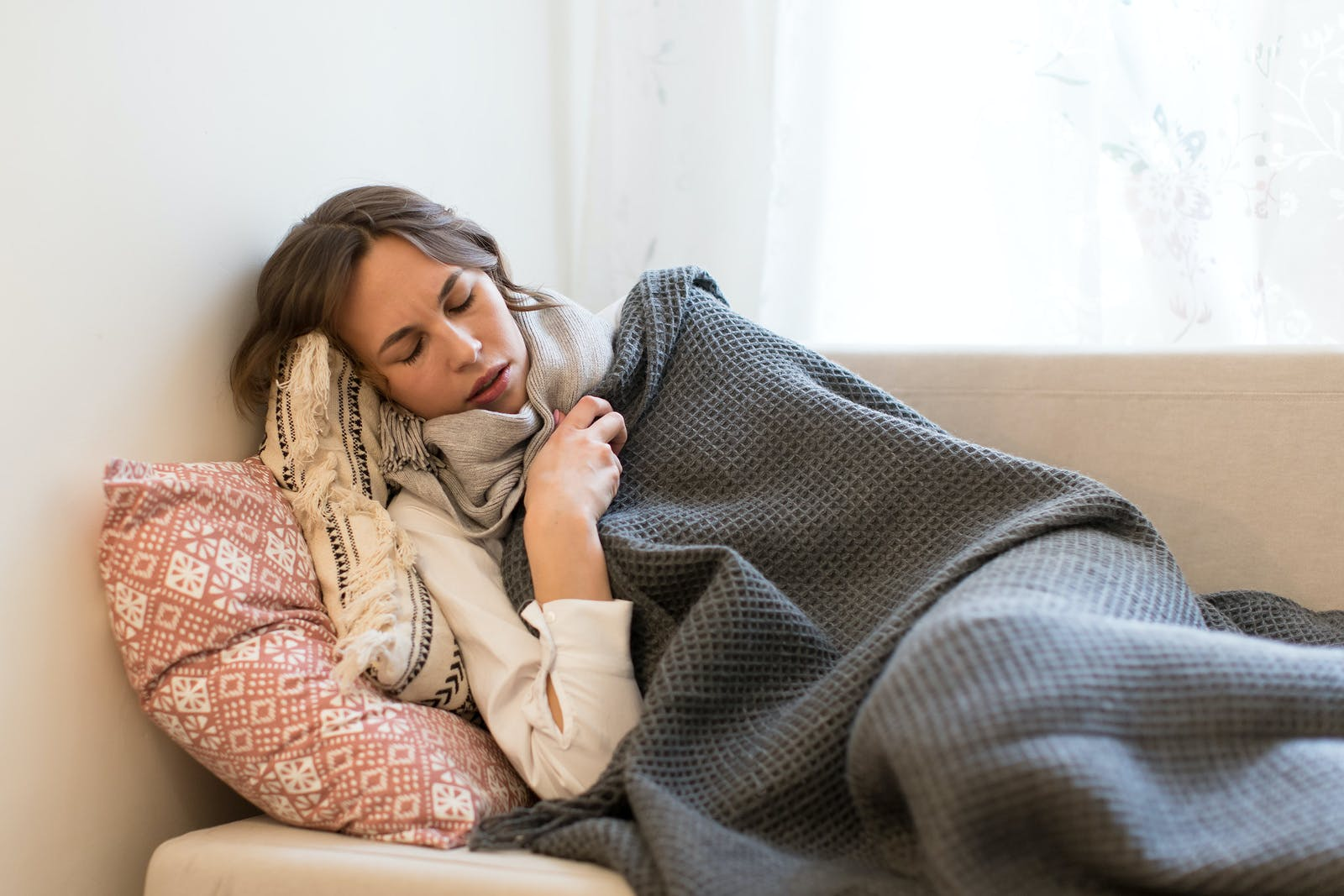 Sick young Caucasian woman lying on sofa and trembles, wrapped in coverlet and scarf, tries to warm herself ,having flu symptoms, feels cold, indoors/Cold, virus, sickness concept/Flu season