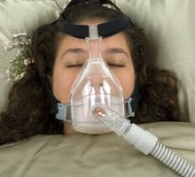 anti-snoring device, sleeping woman with CPAP machine on nose and mouth