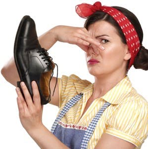 Beautiful vintage housekeeper holding a smelly shoes with facial expression on white