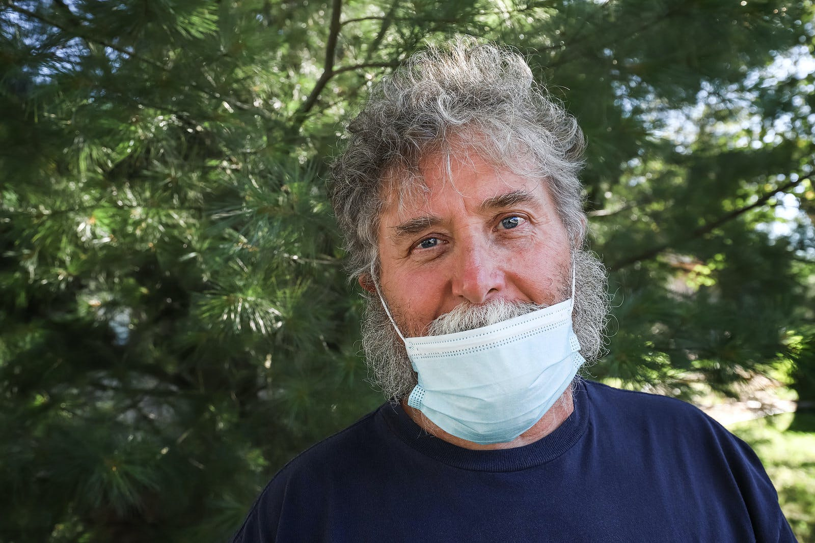 Gray-haired man wearing surgical mask pulled below his nose but over his beard