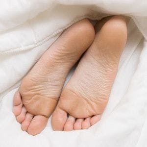 soles of feet poking out from under the covers