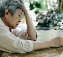 Older woman leans on table with fatigue, possibly due to COVID-19 symptoms lasting