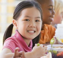 three young children eating lunch with vegetables