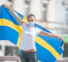 Girl holding flag of Sweden wearing a face mask