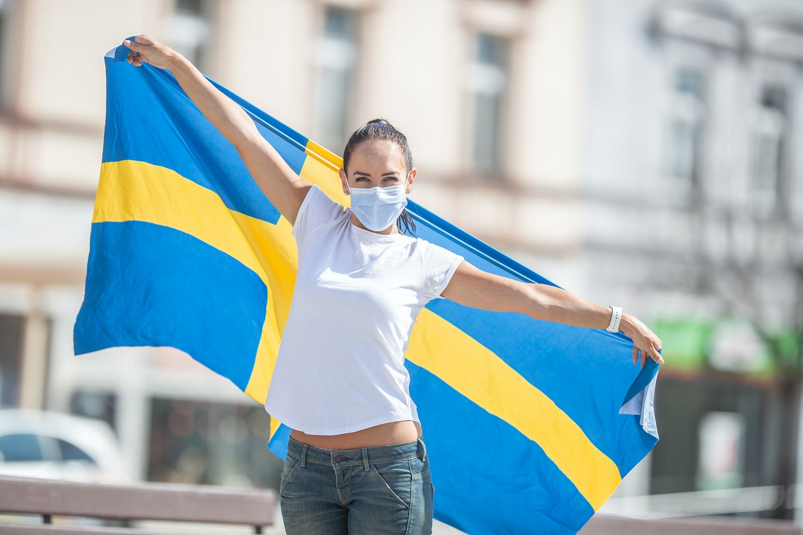 Beautiful smiling Swedish girl holds a flag while wearing a protective face mask outdoors.
