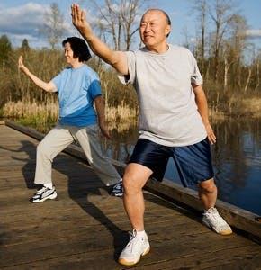 two seniors practice tai qi (tai chi) outdoors