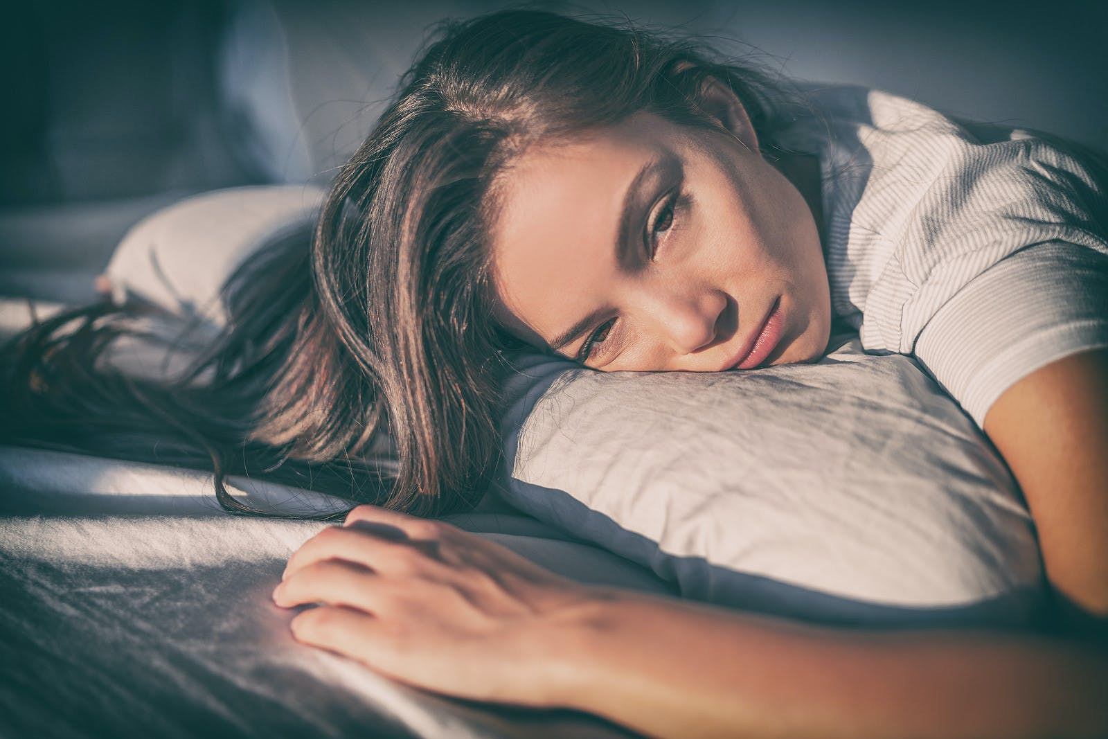 Woman in bed with fatigue feels bad after COVID-19