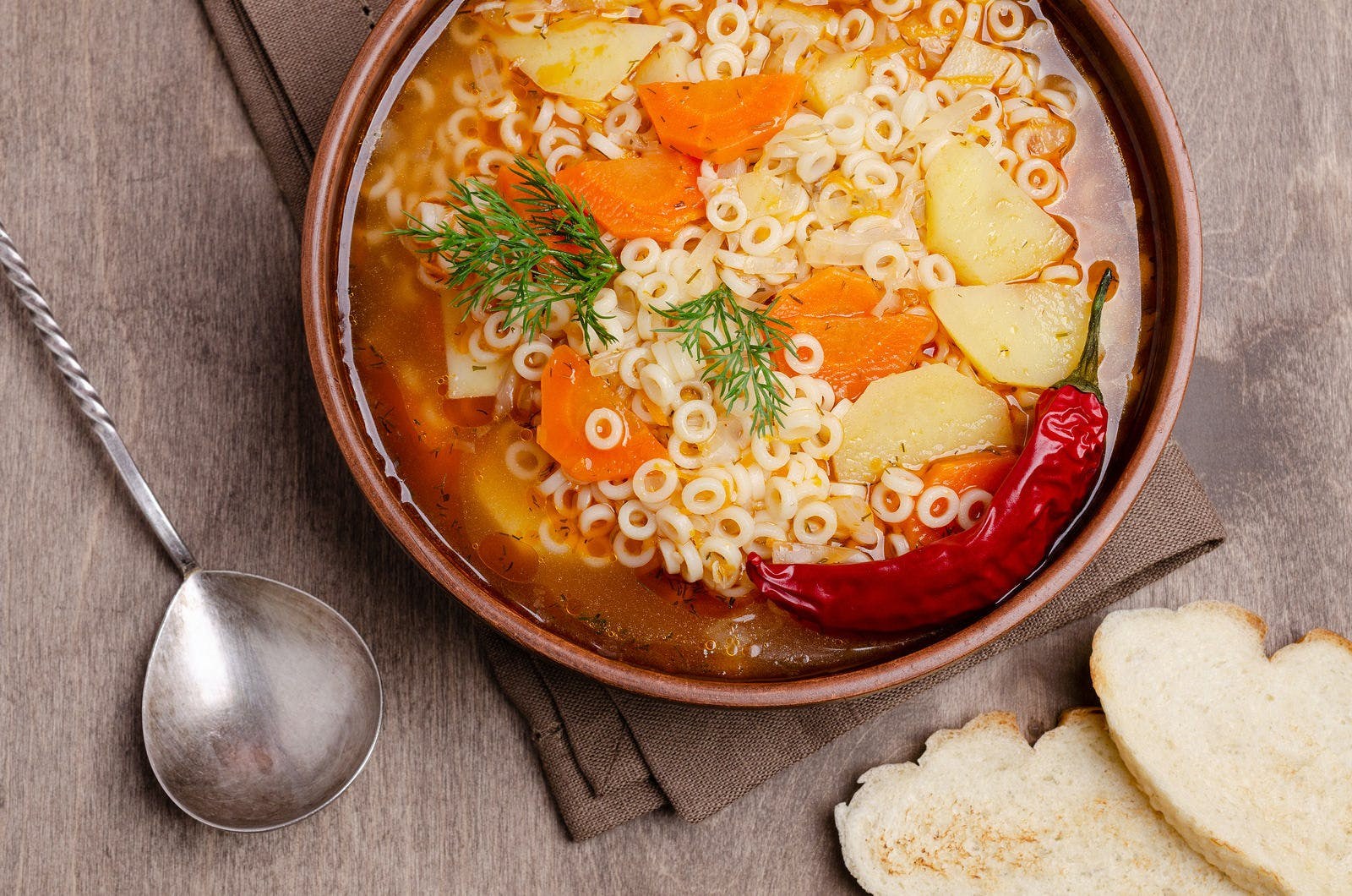 Thick vegetable soup with pasta in a ceramic bowl on a wooden background. Selective focus.