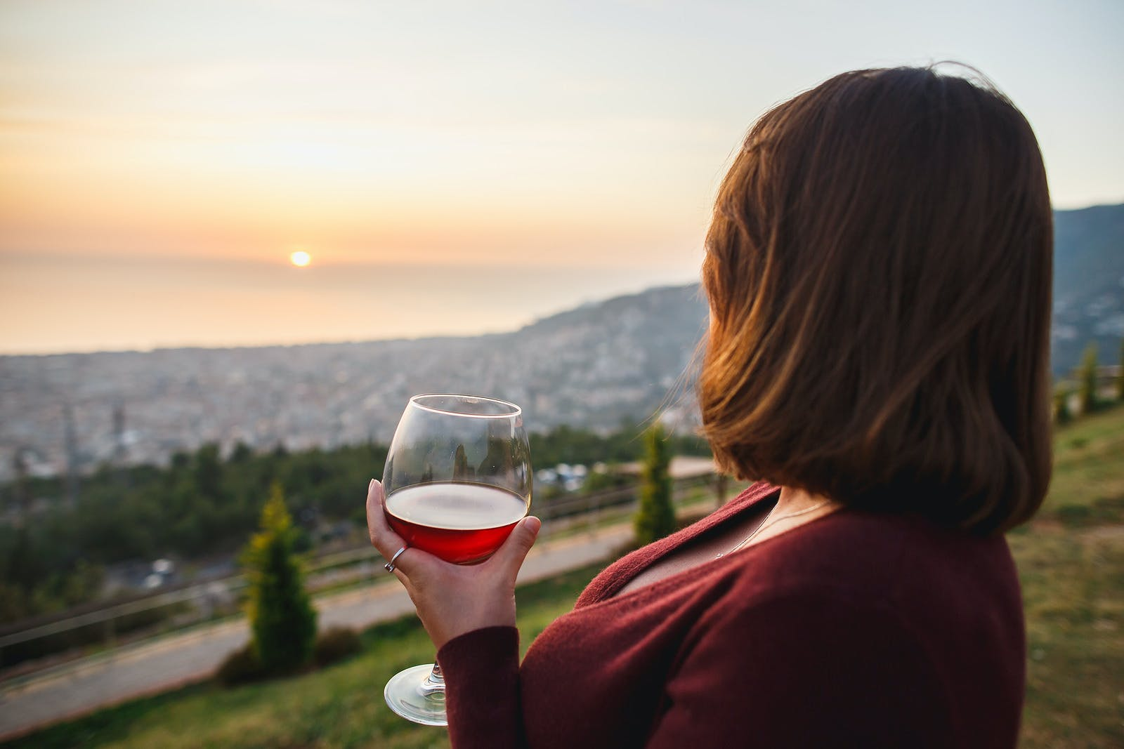 Woman drinking red wine on sunset mountains, close up of hand holding glass of wine. Elegant woman enjoying beautiful mountain and sea landscape on sunset