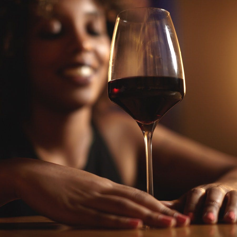 Cropped shot of dark skinned female touching glass of red wine with both hands selective focus on drink. Black woman with Afro hairstyle sitting at bar smiling waiting for friend to join her later