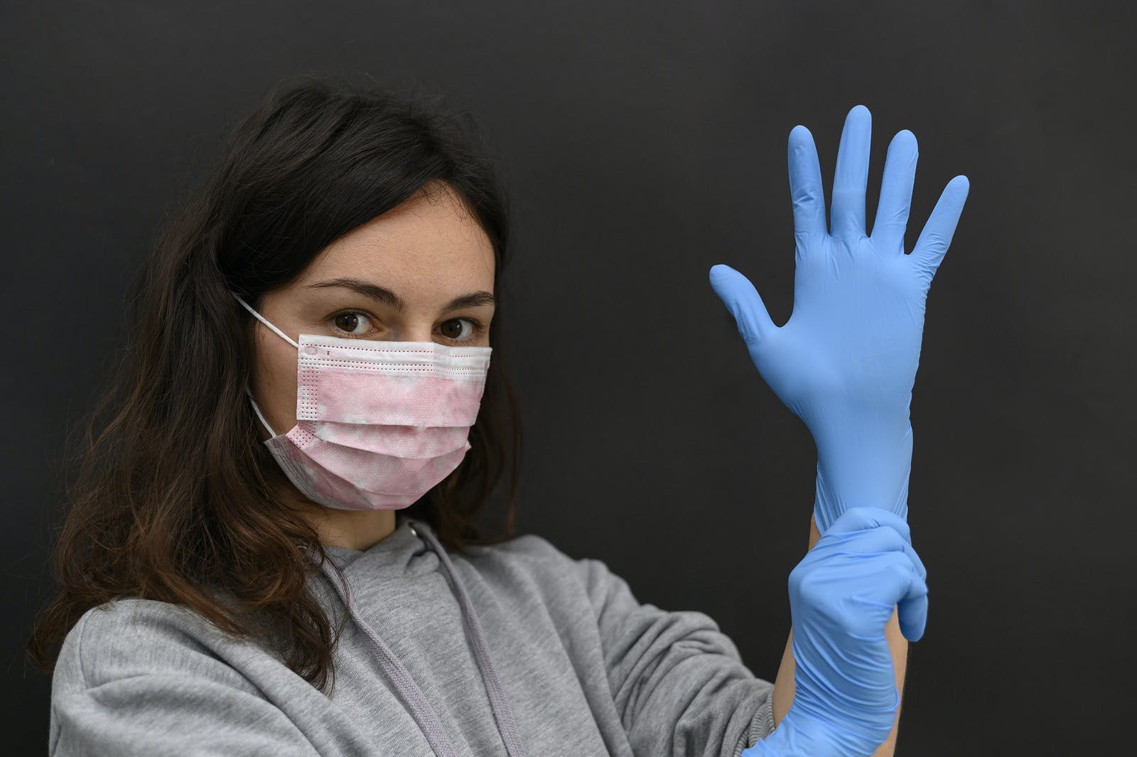A brunette woman puts on her left hand a blue medical disposable glove. Both hands in gloves. Girl wears a protective mask. A piercing glance at the camera. Remedies for viral infection.
