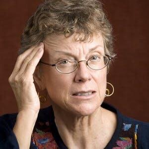 Senior woman with a headache rubbing her temple