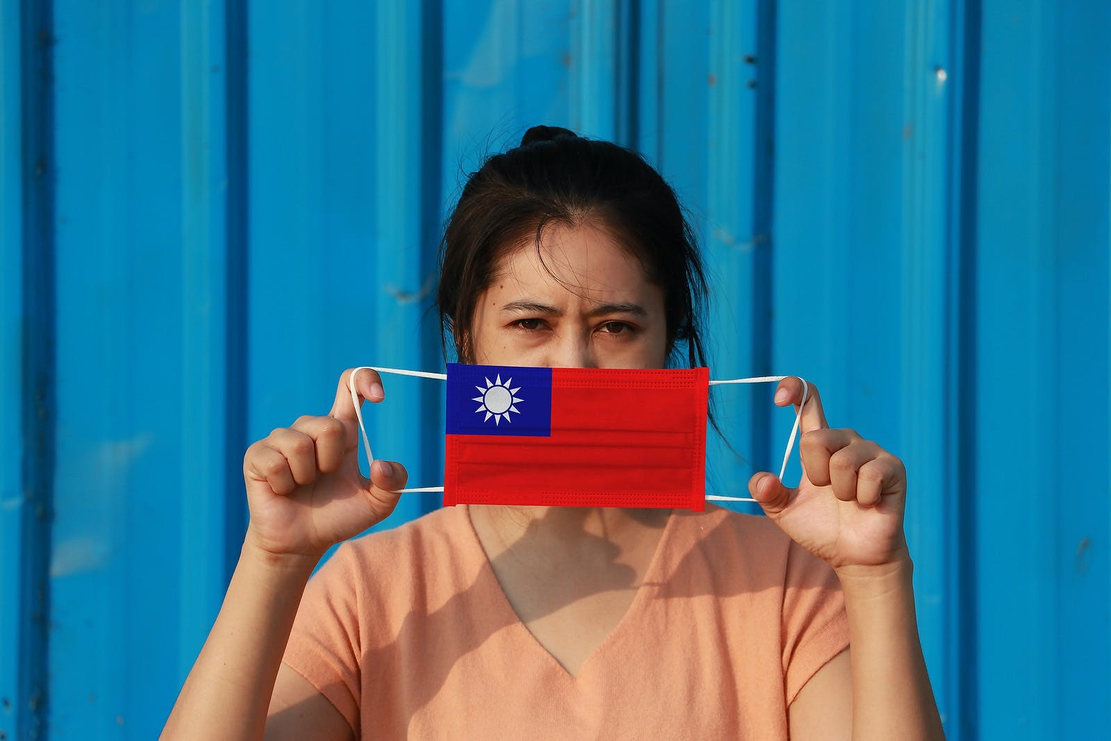 Woman holding up face mask with Taiwan flag