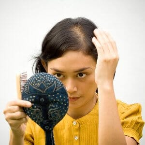 young woman checking her thinning hair in a mirror