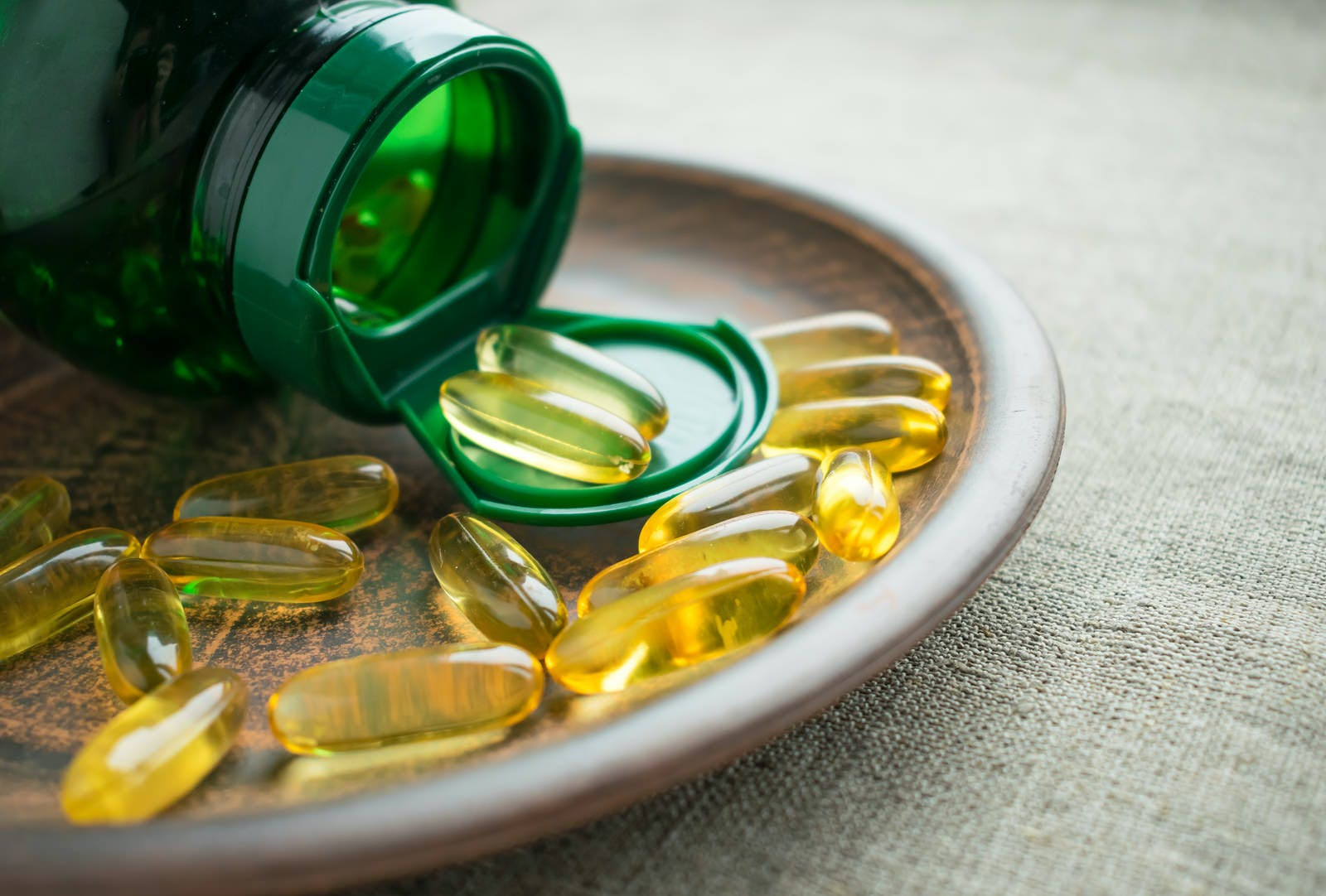 Yellow vitamin D3 (cholecalciferol) gelatine capsules and green bottle on clay plate on burlap background. Vitamin D3 (cholecalciferol) nutrient  beneficial for supporting bone health