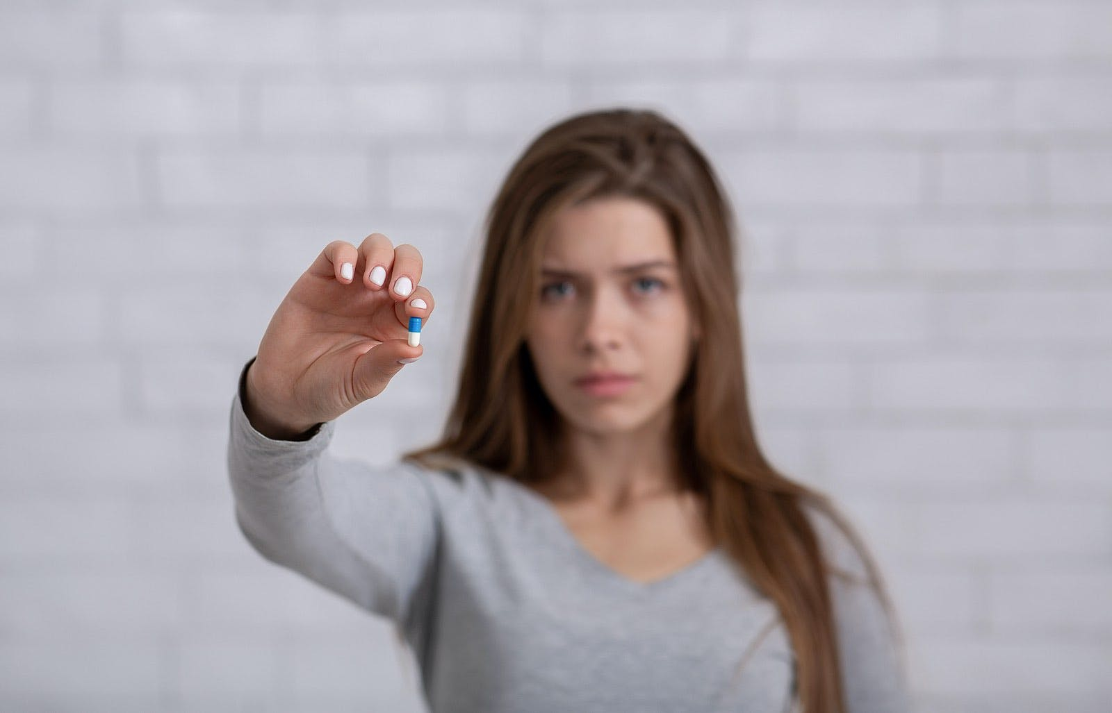 Depressed young lady showing antidepressant or sedative tablet against white brick wall, selective focus. Copy space. Treatment of mental disorders with psychiatric medications
