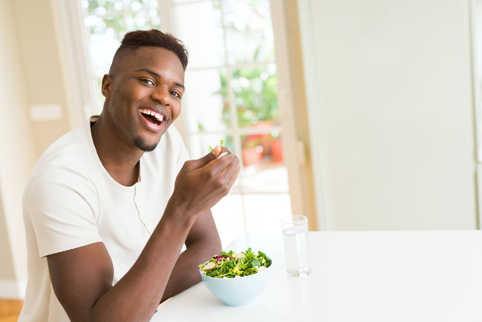 Handsome african young man eating a healthy vegetable salad using a fork to eat lettuce, happy and smiling sitting on the table