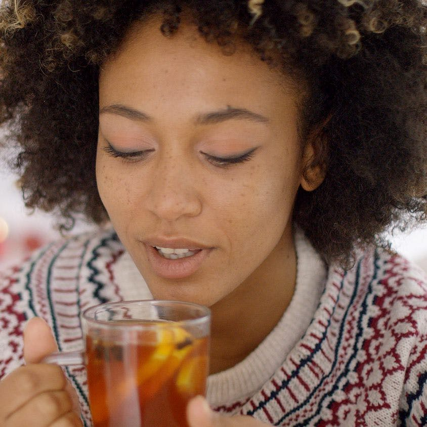 Young woman sipping a cup of hot oolong tea