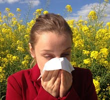 woman with spring allergies blowing nose in a field of wildflowers