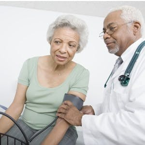 Male doctor & female patient measuring her blood pressure