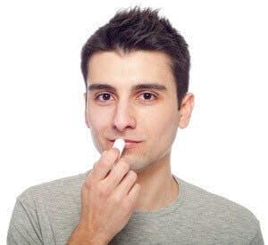man applying lip balm