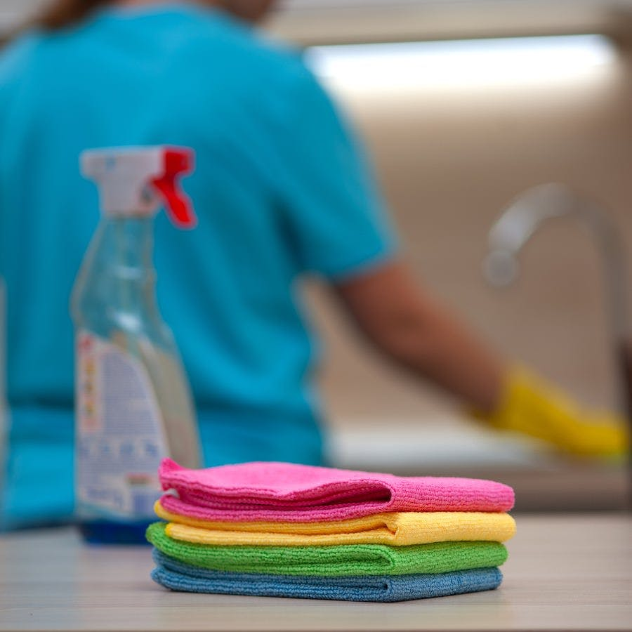 House cleaning. Stack of rags and cleaning liquid on the background of an unidentified young blurry woman in rubber gloves wipes kitchen furniture