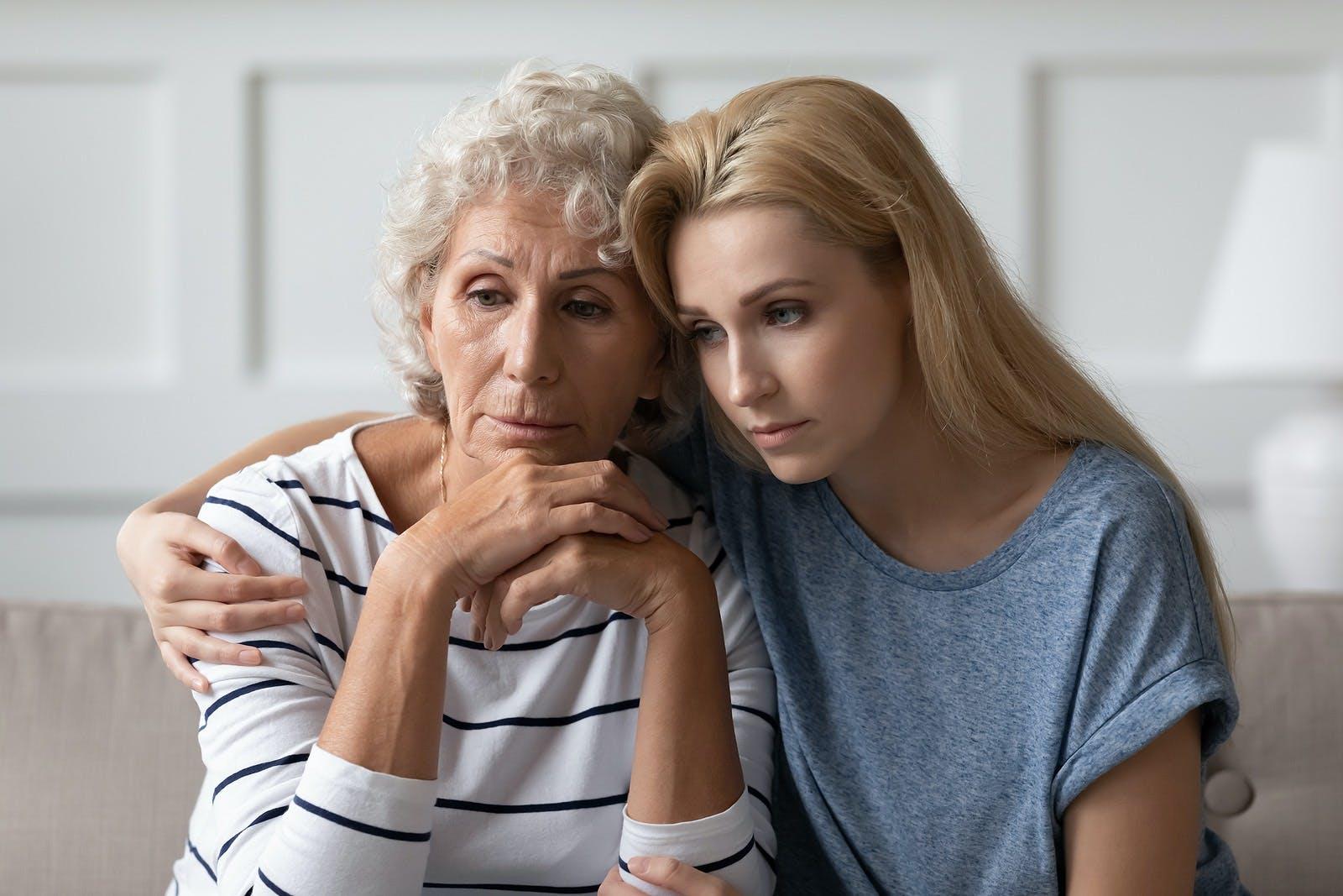Sad grownup daughter sitting on sofa hugging desperate elderly mother