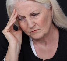 older woman hand to head looks confused; neurological effects of COVID-19