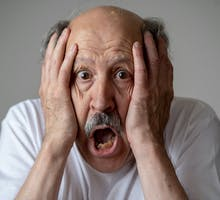 A disoriented man with memory problems and dementia holding his face is dismay