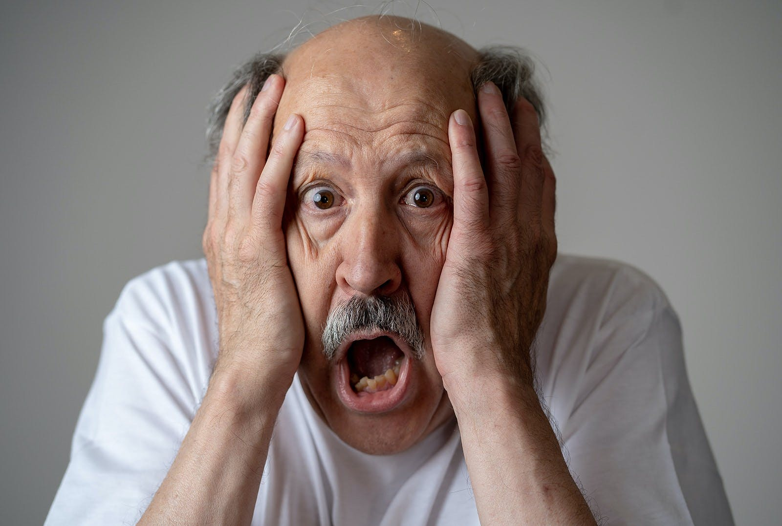 Close up portrait of senior man looking confused and lost suffering from dementia, memory loss or Alzheimer in Mental health in Older Adults and later life concept isolated on grey background.