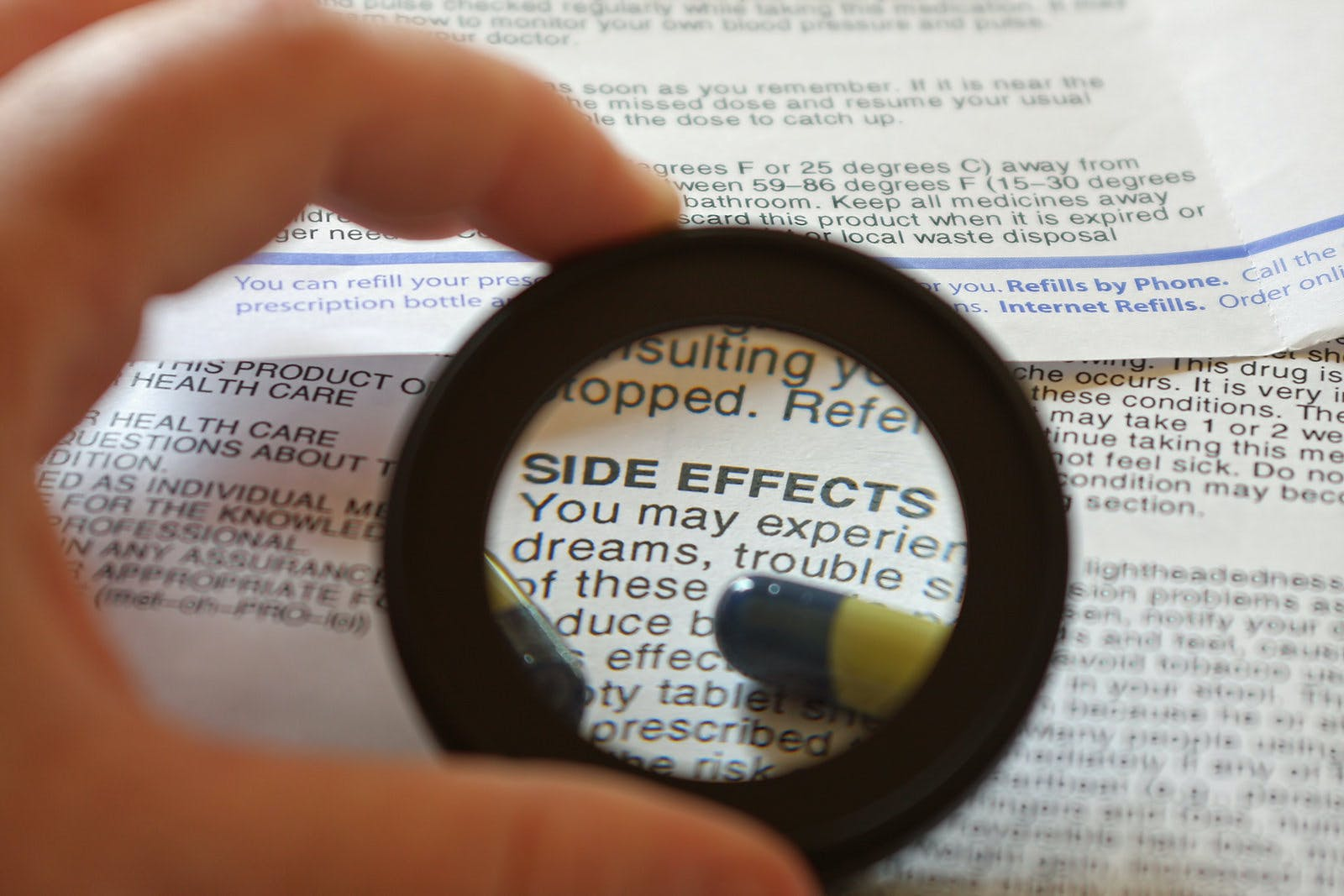 list of drug side effects with magnifying glass