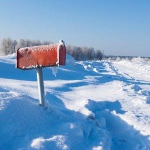 a winter frozen mail box under snow