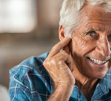 smiling older man wears over-the-counter hearing aids