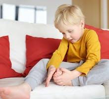 Little boy examines a splinter in his foot