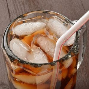 Close up of a soda in a mug with a straw