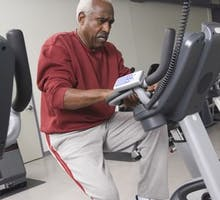 senior man exercising on stationary bike in health club for his workout