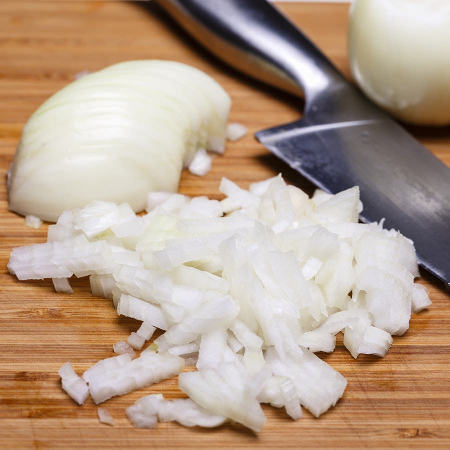 Onion and onion slices on wooden cutting board.