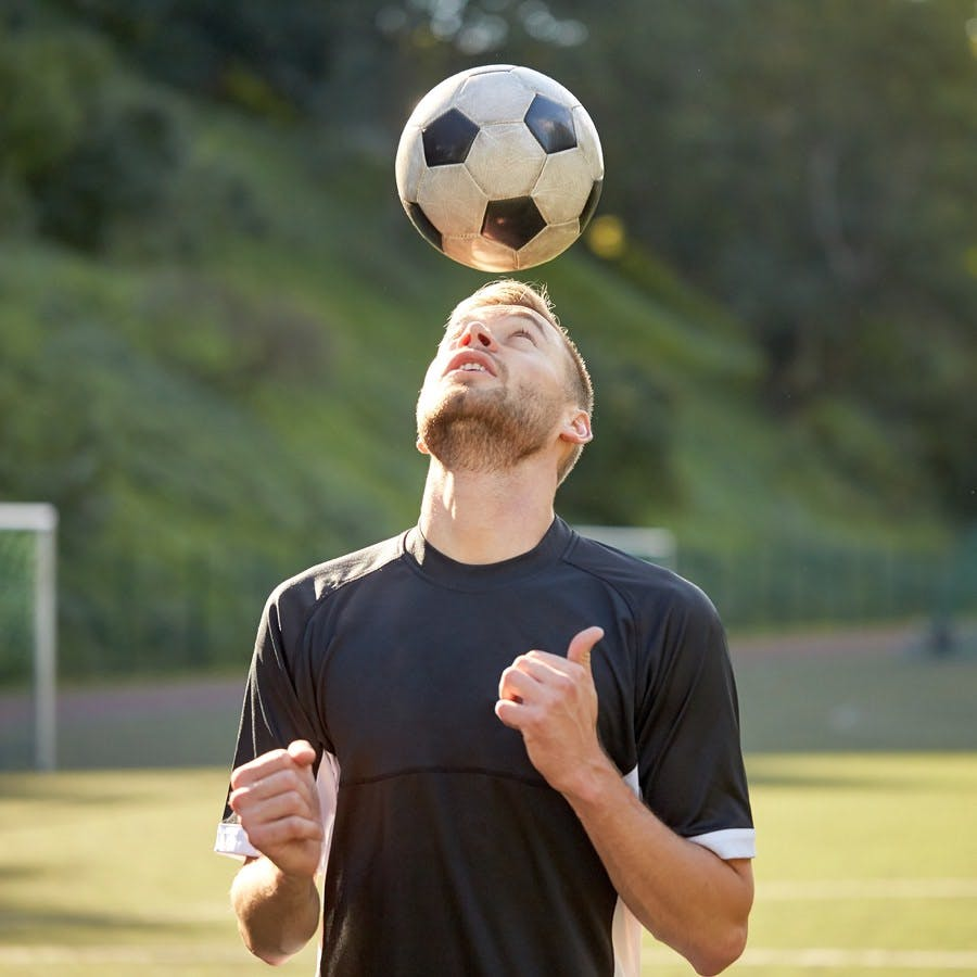Sport, football and people – soccer player playing and juggling ball using header technique on field