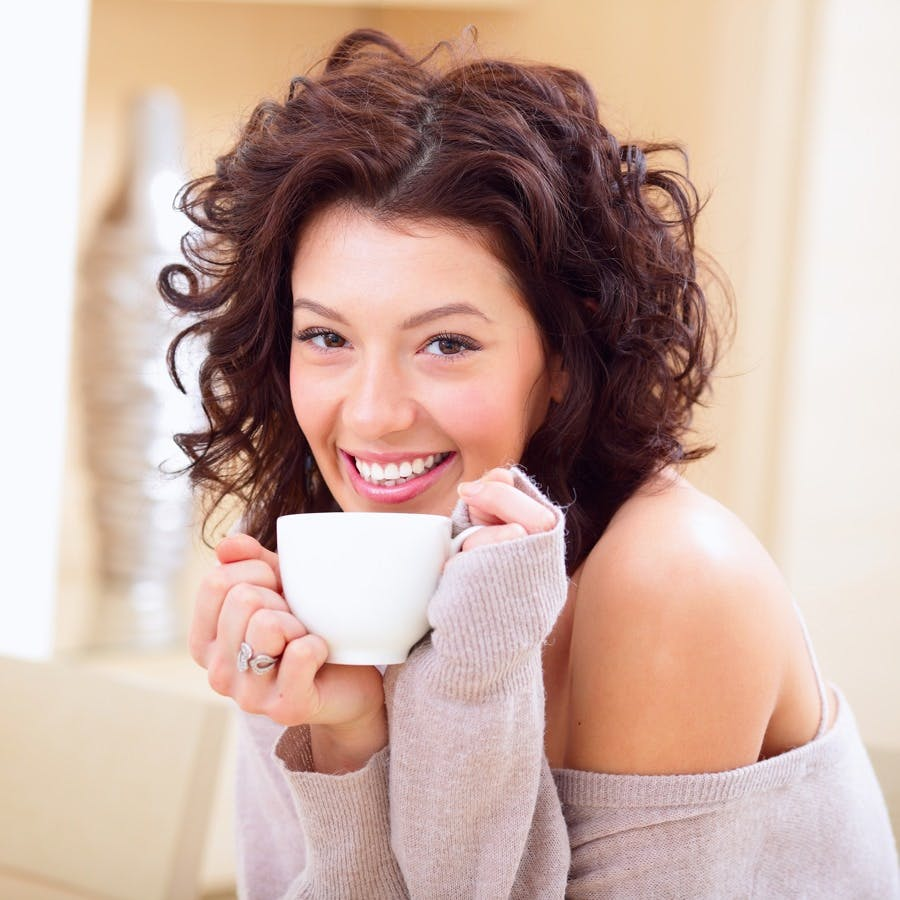 Young woman at home sipping Oolong tea from a cup